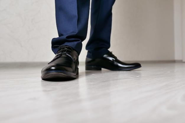 Мужские ноги в черных туфлях крупным планом