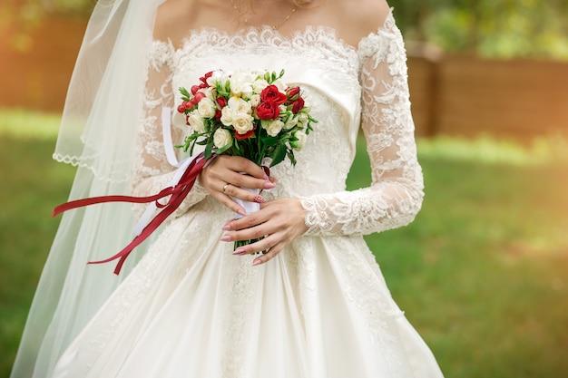 花嫁のクローズアップの手の中のウェディングブーケ