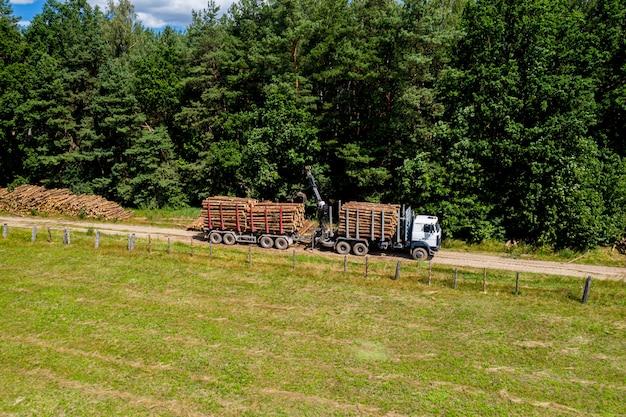 森林破壊と伐採のトップビュー。トラックは丸太を取り除きます。森林産業。