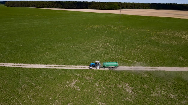Трактор с прицепным полем для удобрения натуральным навозом