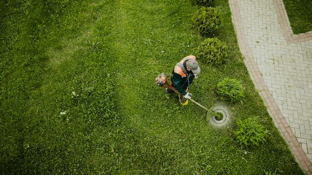 芝刈り機の男は芝生の上からの眺めを刈る