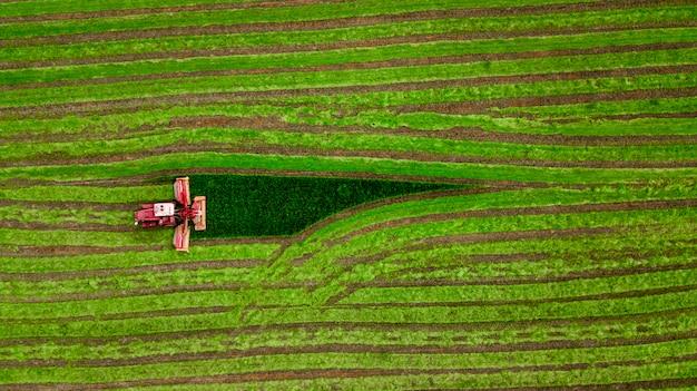 トラクターは、緑のフィールドの空撮で草を刈る