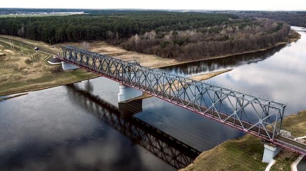 ドローンと川の空中写真に架かる鉄道橋