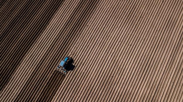 フィールドを耕している青いトラクター。ドローンによる空撮