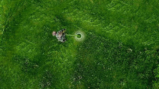 芝刈り機で草を刈るトップビュー男性労働者。
