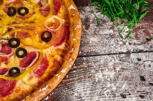木製のテーブルに野菜とチーズのおいしいピザ