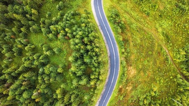 Вид с воздуха на извилистой дороге среди леса и деревьев. закатное поле в литве.
