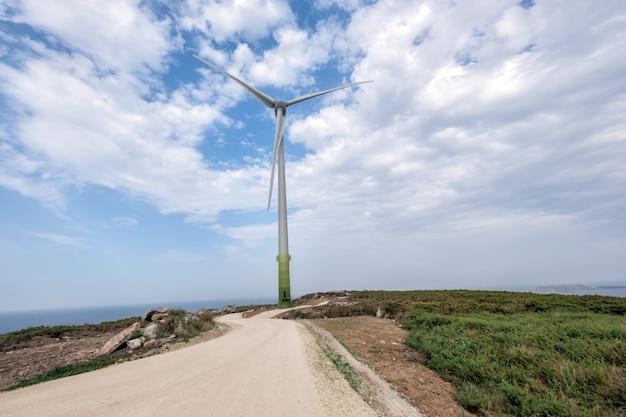 海の近くの緑の野原で巨大な電気風車の空中ドローンショット