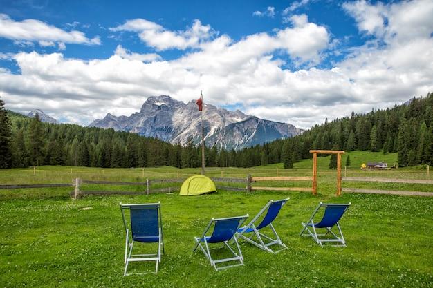 Красивая природа в северных скалистых горах канады. два красных удобных шезлонга на озере
