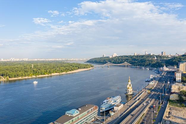 Вид с воздуха на реку днепр, киевские холмы и город киев возле пешеходного моста, украина