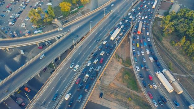 都市交通-都市道路のラッシュアワーの交通。高速道路の道路の交差点を持つ近代的な大都市。大都市での道端の交通渋滞、交通機関の動き。