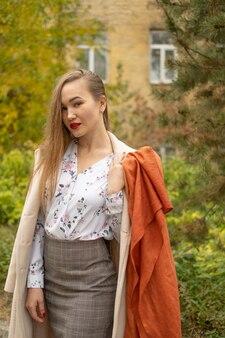 スタイリッシュな古典的な服を着ている若い美しい女性のストリート写真。下へ見ているモデル。女性のファッションのコンセプト。