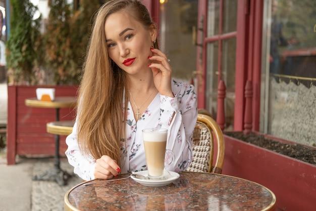 パリのストリートカフェでコーヒーを飲む若い女性
