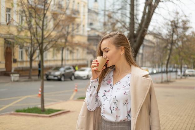 秋の街を歩いて飲む若い女性は、紙コップでコーヒーを奪います。
