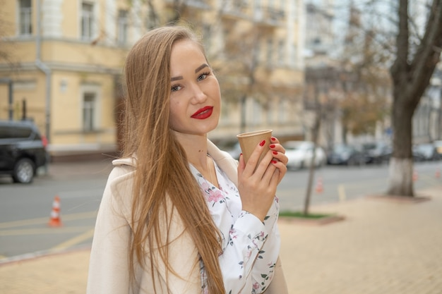 Молодая женщина гуляя в улицу города осени и выпивая забирает кофе в бумажном стаканчике.
