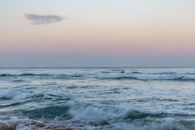 夕暮れ時の海岸の海の波