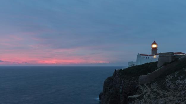 日没時のセントビンセント岬の灯台と崖の眺め。大陸ヨーロッパの最も南西のポイント、サグレス、アルガルヴェ、ポルトガル。