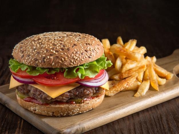 Свежий вкусный гамбургер и картофель на деревянной доске