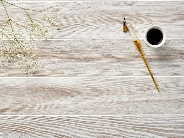 Перо и чернила каллиграфии на деревянном белом столе.