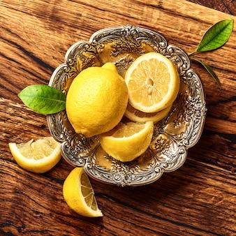 オークの木製テーブルの上の葉でレモン。果物のトップビュー。