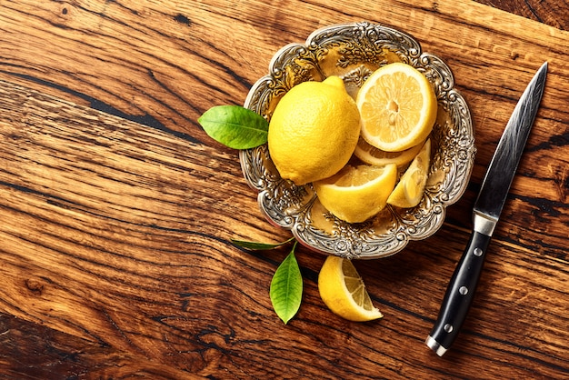オークの木製テーブルの上の葉でレモン。デザインまたはテキスト用のスペースをコピーします。ナイフで果物の平面図です。