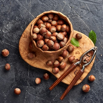 Фундук с щелкунчиком на оливковой деревянной доске. орехи с зелеными листьями. вид сверху.