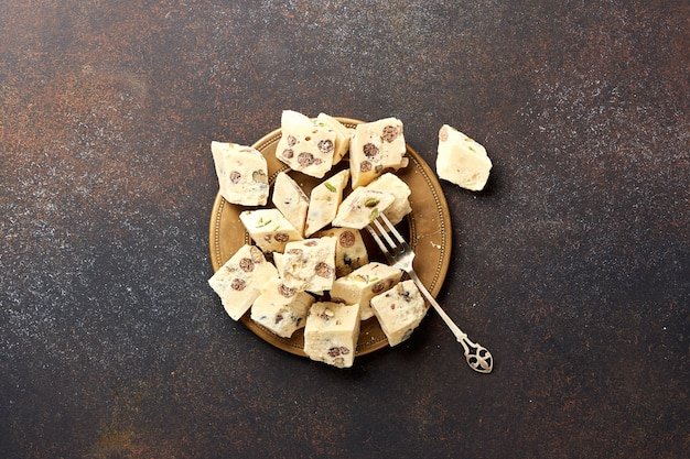 Восточный деликатес. халва, сладость, десерт на коричневом фоне.
