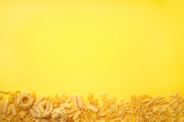 Ассорти видов макарон на желтом фоне