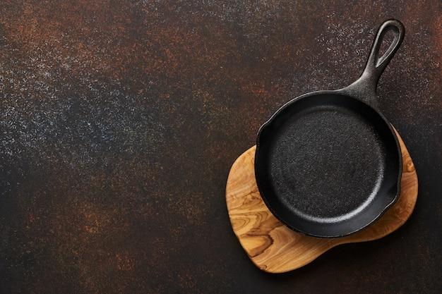 Чистый черный жареный лоток на оливковой деревянной доске по коричневому конкретному фону с пространством копии.