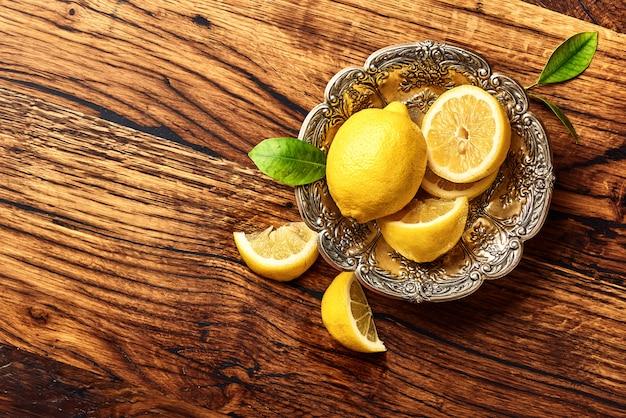 Лимоны с листьями на дубовый деревянный стол. скопируйте пространство для дизайна или текста. вид сверху на фрукты.