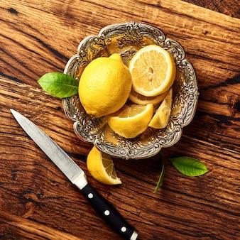 Лимоны с листьями на дубовый деревянный стол. вид сверху фруктов с ножом.