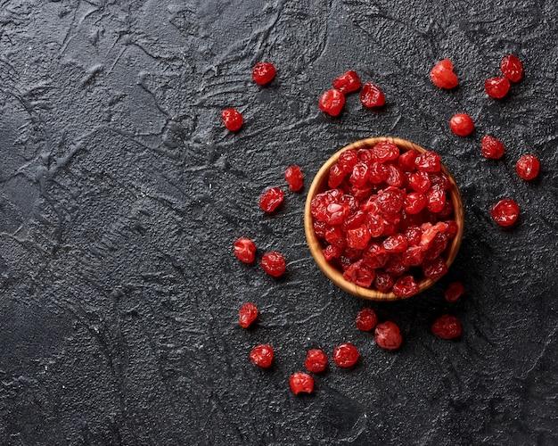 Сушеные красные вишни на черной поверхности с копией пространства.