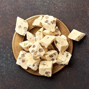 Восточное лакомство халва, сладость, десерт на коричневой поверхности.