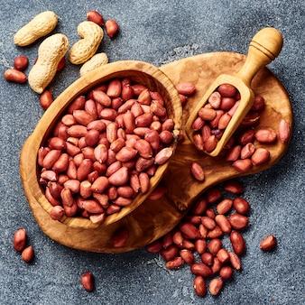Очищенные арахис в миску и совок на серой поверхности. вид сверху орехов.