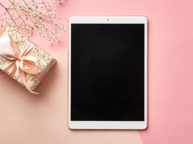Цифровой планшет на розовом столе