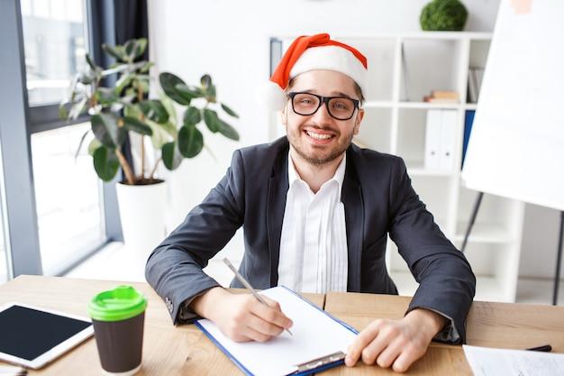 Молодой веселый бизнесмен в офисе.