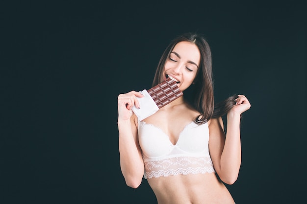 幸せな女はチョコレート・バーを保持しています。長い黒髪の若い女性が立っているスタンド。その女の子はスポーツの姿をしていて、白い下着を着ています。