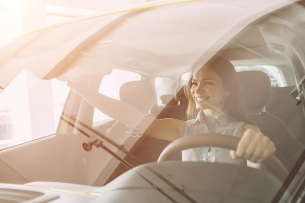 ディーラーで車を買う美しい若い女性。車のインテリアに座っている女性モデル