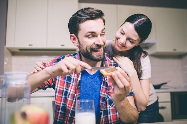 慎重な少女が男の後ろに立って、彼に目を向ける。彼女は微笑みます。男はトーストにチョコレートペーストをかけ、彼女を見ます。彼も笑顔です。彼らは満足している。