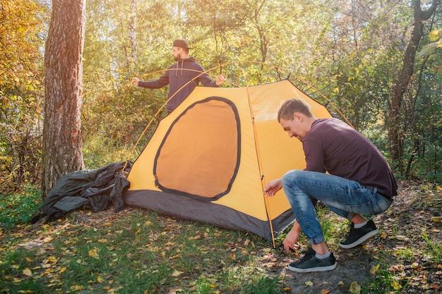 Изображение двух молодых людей в лесу положить палатку. один парень работает с веревками. еще один стенд позади палатки. они работают вместе