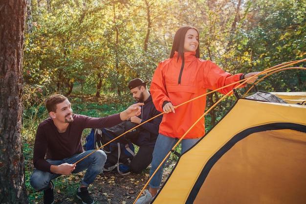 Веселая молодая женщина держит палатку веревку и улыбки. парень сидит в отряде и помогает ей. второй молодой человек работает один.