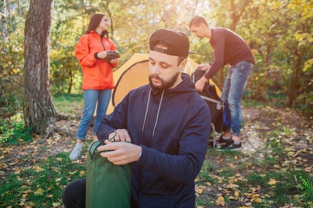 Бородатый молодой человек держит спальный мешок и смотрит на него. он серьезен. женщина держит в руках радио. другой парень работает с палаткой.