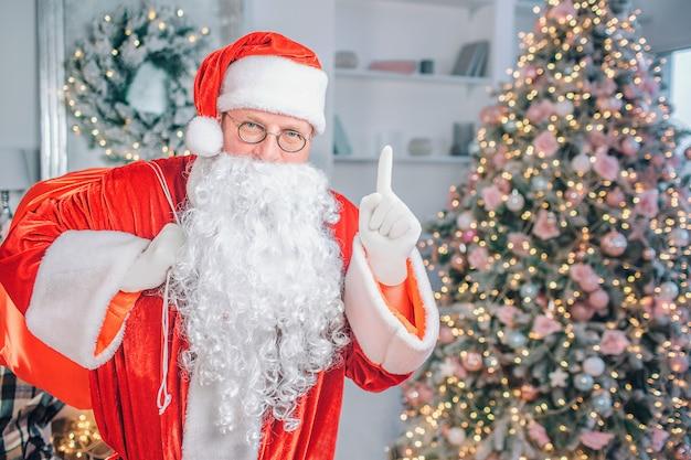 成熟したサンタクロースが立ち上がって指します。彼は真剣に見える。彼の後ろにクリスマスツリーがあります。