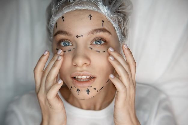 若い女性が彼女の顔と外観に触れます。彼女は肌に跡があります。モデルが集中。