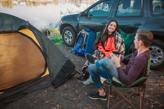 Веселый молодой мужчина и женщина сидят вместе на складных стульях и смотрят друг на друга. они держат чашки в руках. молодая женщина покрыта одеялом. они сидят у машины и палатки с оборудованием.