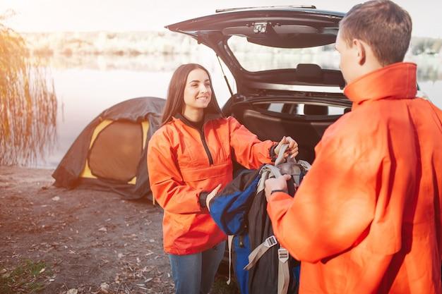 Милая молодая женщина в оранжевой куртке смотрит на парня и берет у него рюкзак. она улыбается. молодой человек смотрит на нее. они находятся возле машины и палатки. они упаковывают вещи.