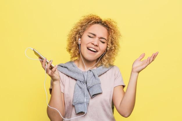 Эмоциональная девушка слушает музыку на телефоне. она наслаждается моментом и поет песню.