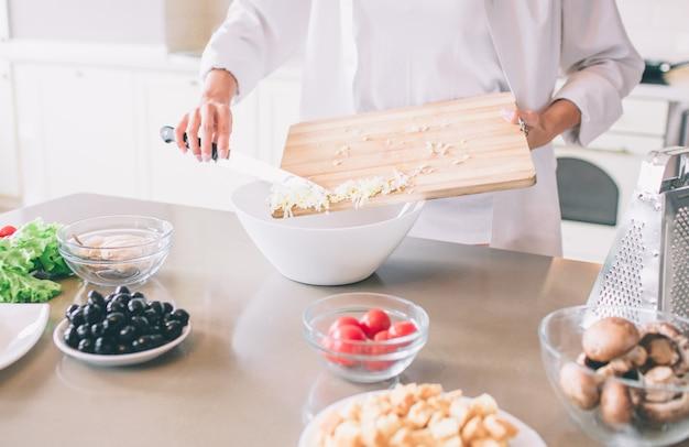 白いボウルに食事を入れて女性の手のビューをカットします。彼女はそのためにナイフを使用します。女の子が料理しています。