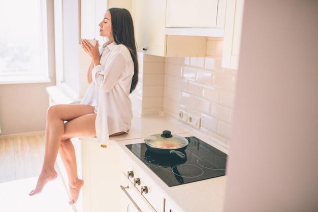 ゴージャスなボディを持つ美しい少女は、ストーブの近くのテーブルに座って、調理される料理を待っています。彼女は足を組んでいます。
