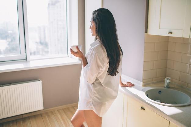 Красивая и потрясающая девушка стоит на кухне и смотрит в окно. она сильная и хорошо сложенная. девушка позирует
